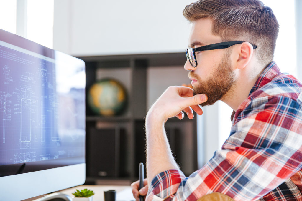 Profile of concentrated bearded man in glasses sitting and drawing blueprints on computer