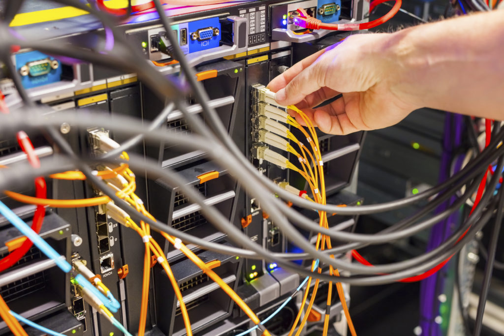 Closeup of IT technician's hand plugging fiber channel cable into switch in datacenter