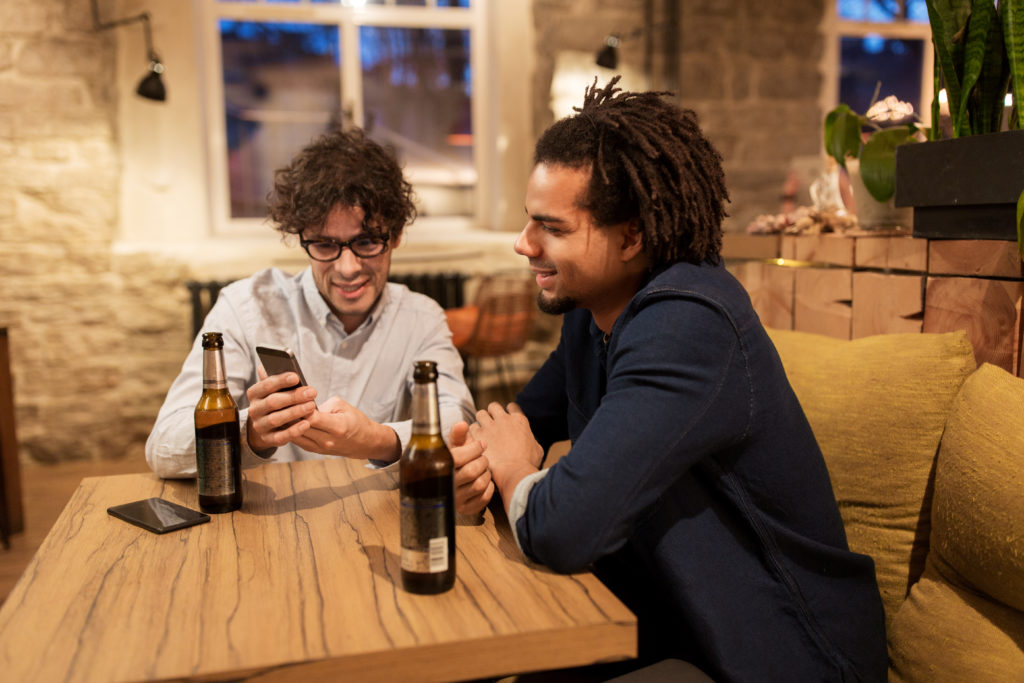people, men, leisure, friendship and technology concept - happy male friends with smartphones drinking bottled beer at bar or pub